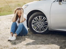 Worried Young Woman Sitting Near Broken Automobile At 4173090